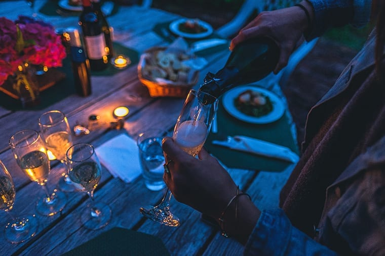 Woman pouring wine on a champagne glass as part of a fancy outdoor dinner.