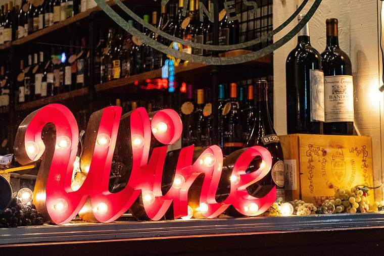 """Bar counter with a letter standee that spells out the word """"wine."""""""