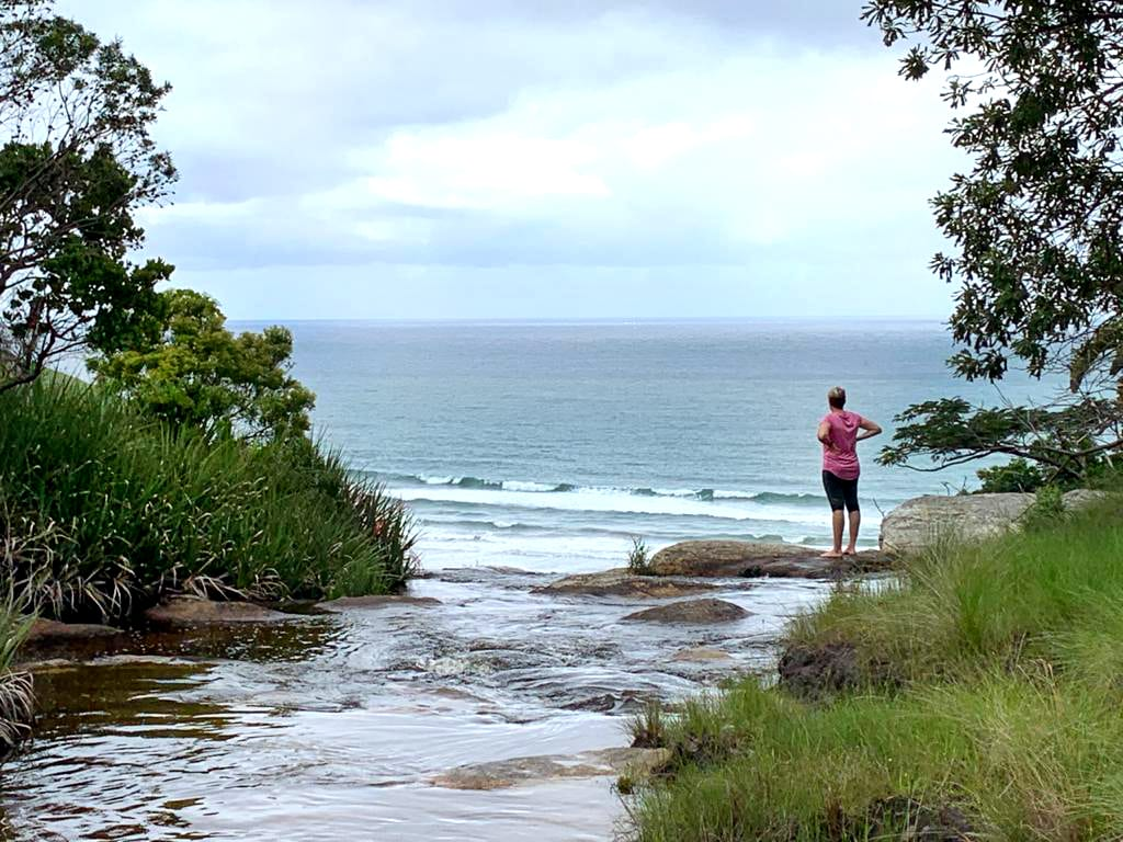 A woman stands at the top of a Pondoland waterfall that drops into the ocean below.