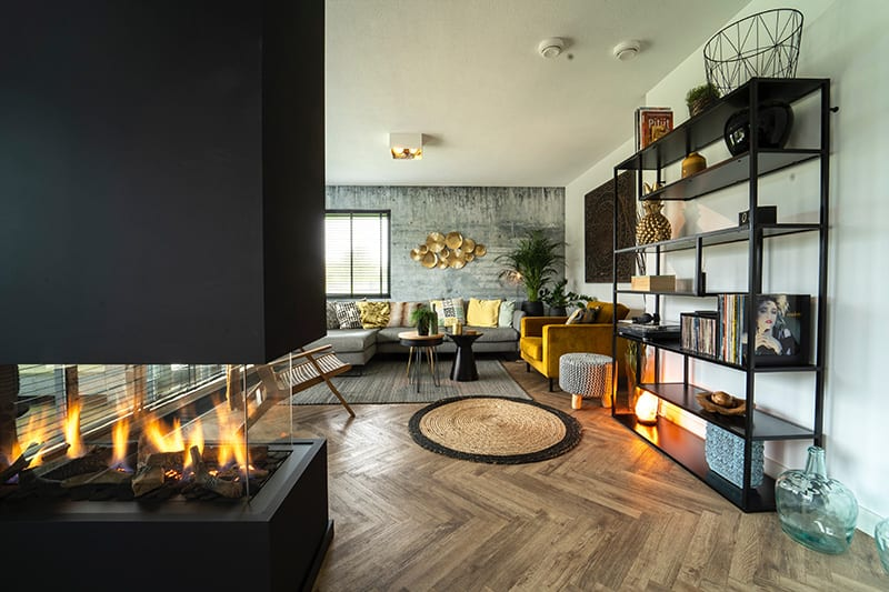 Building a fireplace into a room-dividing wall is a trendy way to maximize the heat distribution while enjoying the view of the fireplace from different angles.