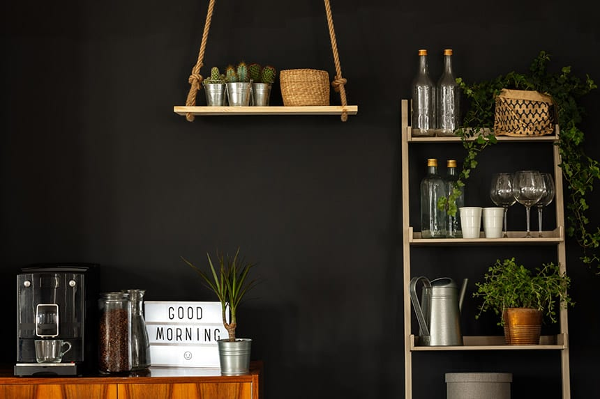Modern coffee and wine station with shelves, plants, coffee machine and wine glasses on a black wall
